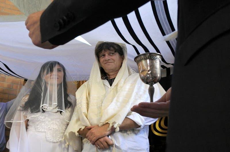 Rabijn die Joodse bruid en een bruidegom belssing stock foto's