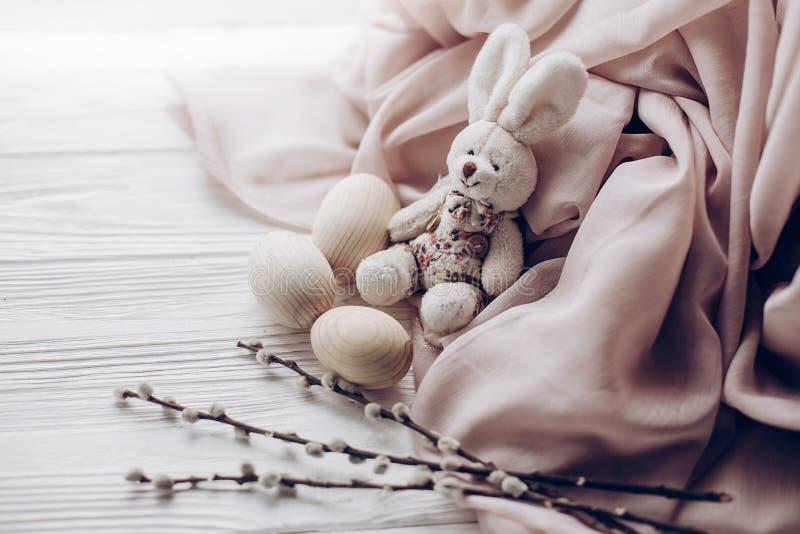 Rabit do coelhinho da Páscoa e ovos e botões à moda do salgueiro no wo rústico foto de stock royalty free