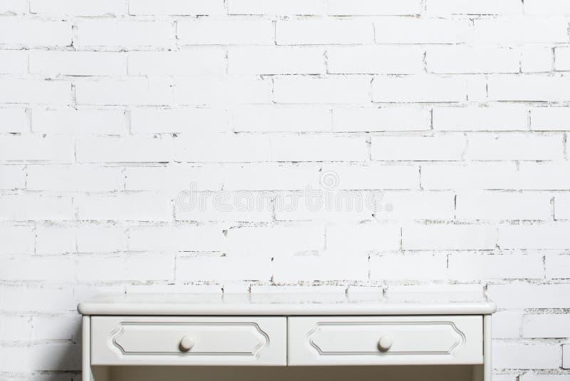 Raboteuse blanche sur le mur de briques blanc images stock