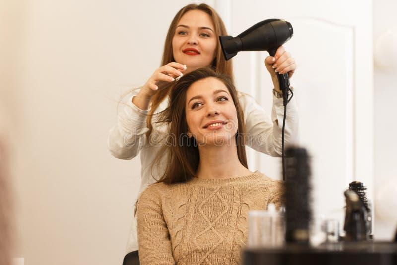 Raboteuse de cheveux faisant le style pour un client féminin images libres de droits