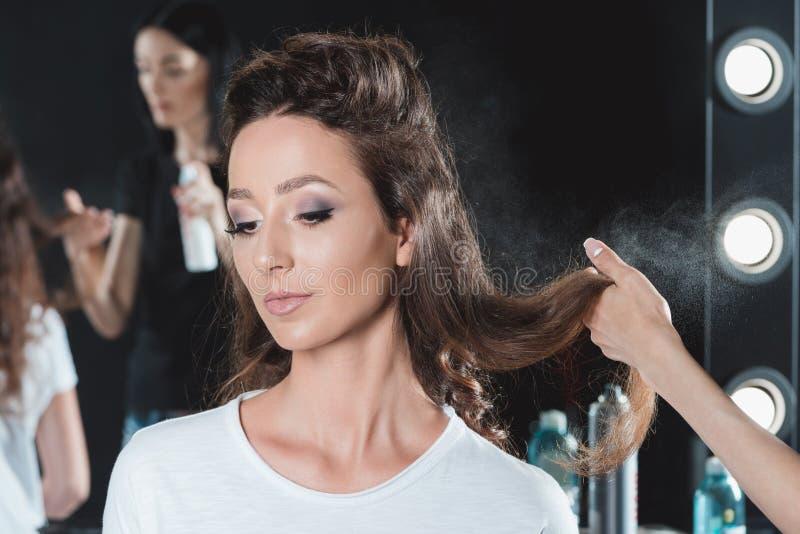 Raboteuse de cheveux utilisant la laque pour finir la coiffure photographie stock