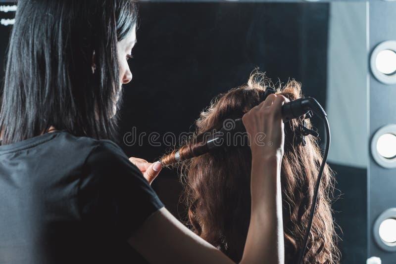 Raboteuse de cheveux utilisant le fer de bordage tout en dénommant des cheveux photographie stock