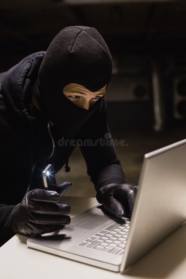 Rabuś sieka laptop podczas gdy robić światłu z jego telefonem obrazy stock
