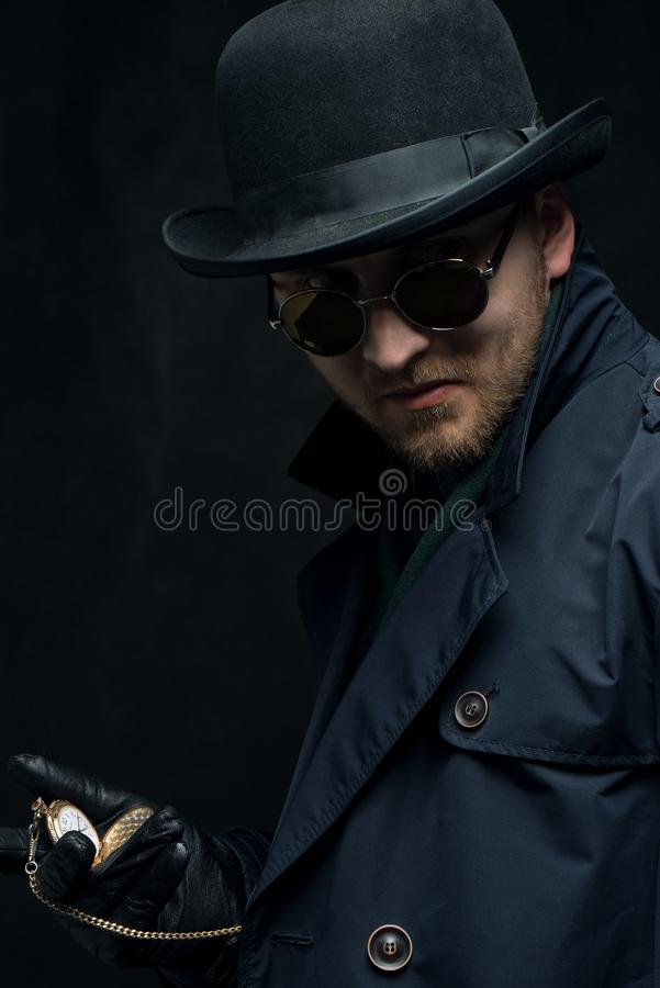 rabunek Rabuś jest ubranym okulary przeciwsłonecznych i rękawiczki trzyma złocistego zegarek w jego rękach zdjęcia stock
