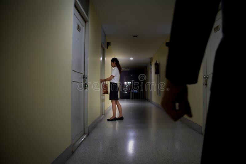 Rabusia lub złodzieja ręka patrzeje biznesowa kobieta otwiera drzwi przy nocą który, ostrość na ludziach, kryminalny pojęcie zdjęcie royalty free