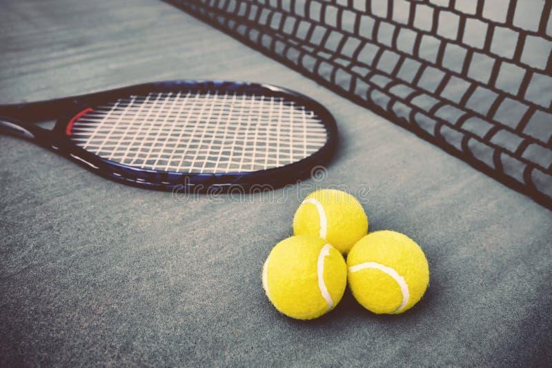 Racchetta di tennis, rete e tre palle fotografie stock