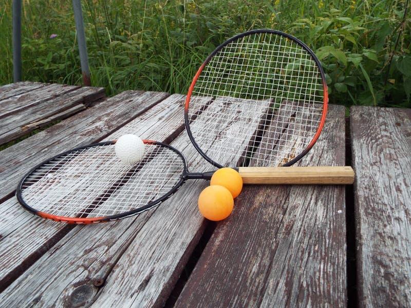 Racchette e palline da tennis di sport su un fondo di legno in natura fotografia stock libera da diritti