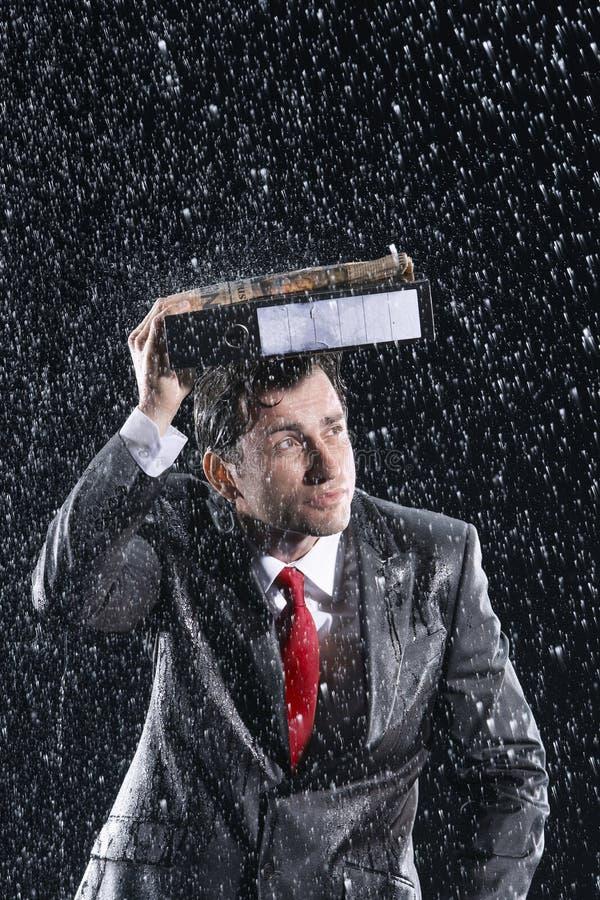Raccoglitore di Covering Head With dell'uomo d'affari in pioggia fotografie stock libere da diritti