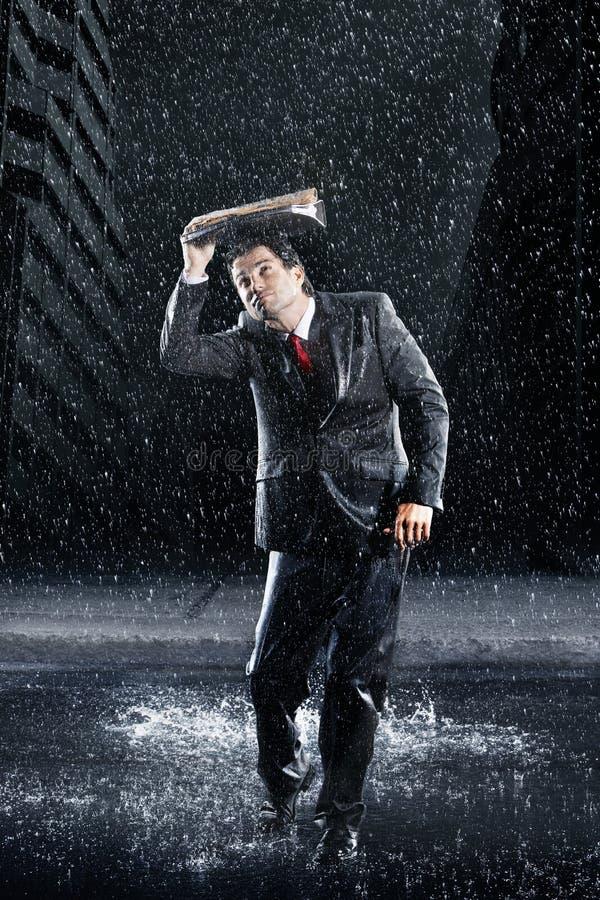 Raccoglitore di Covering Head With dell'uomo d'affari in pioggia immagine stock