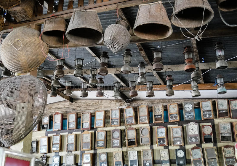 Raccolta degli orologi di pendolo polverosi della parete nel negozio di ciarpame, fondo d'annata fotografia stock