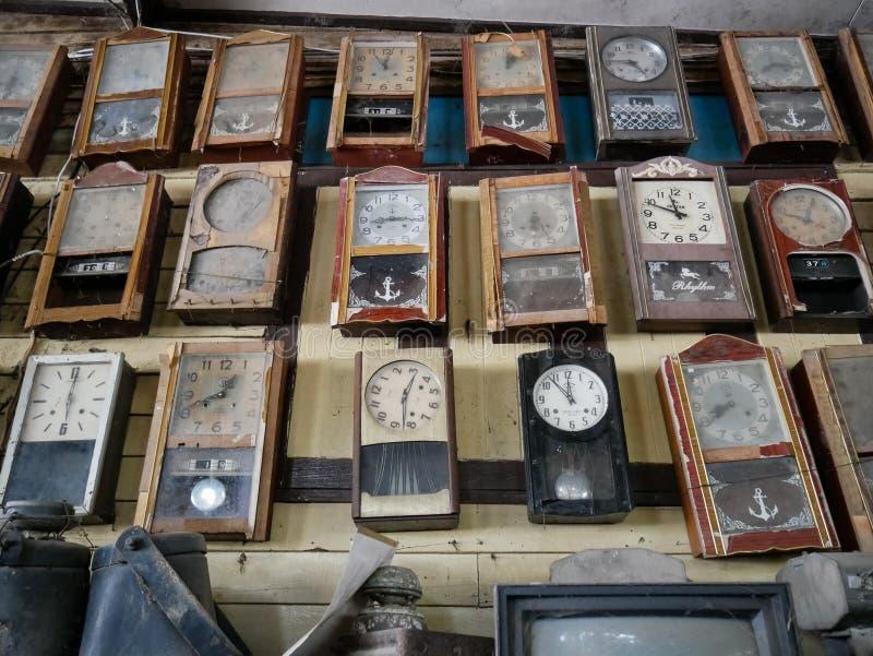 Raccolta degli orologi di pendolo polverosi della parete nel negozio di ciarpame, fondo d'annata fotografia stock libera da diritti