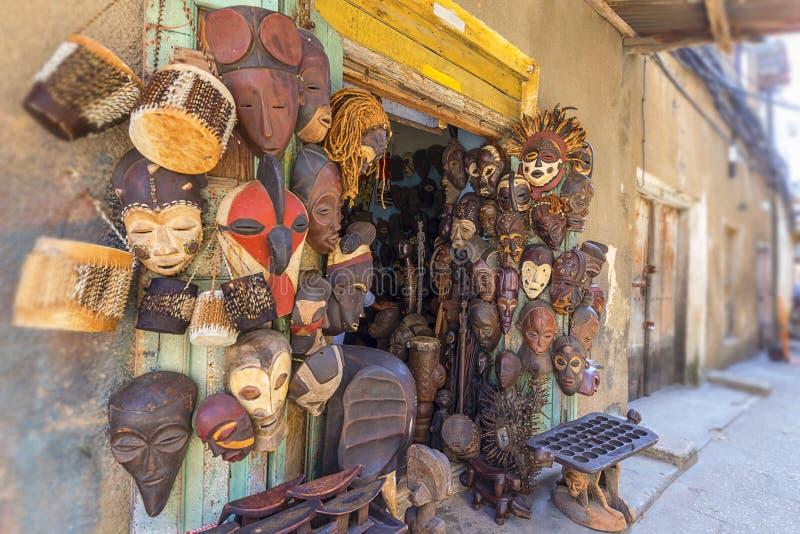 Raccolta delle maschere africane che appendono su una parete all'aperto di shokeepers fotografia stock
