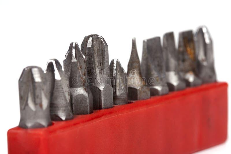 Raccolta di vecchi supporti pungenti arrugginiti per un trapano in una cassa rossa isolata su fondo bianco, macro, primo piano fotografia stock libera da diritti