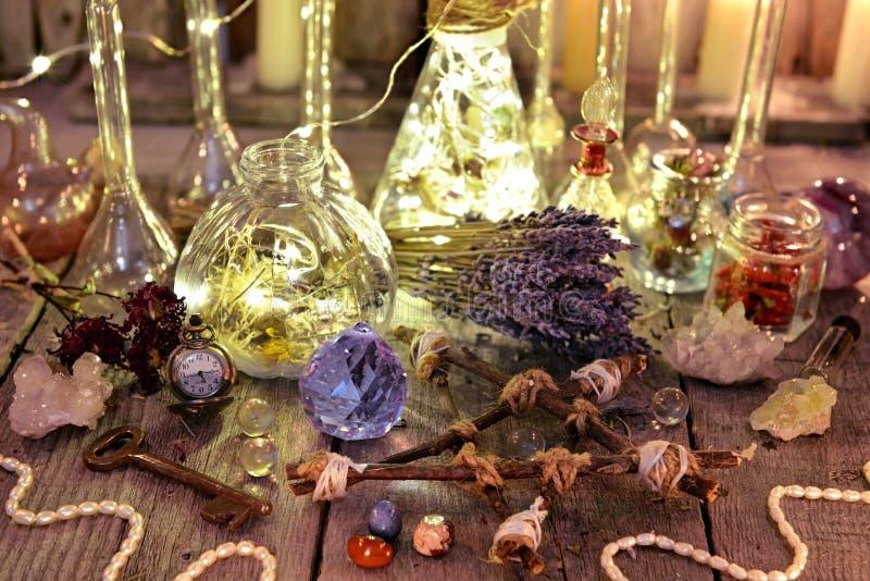 Raccolta magica della strega con le bottiglie del fulmine, i cristalli, il pentagramma, la vecchia chiave e le erbe fotografia stock libera da diritti