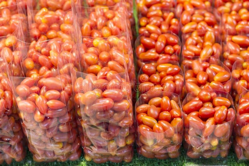 Raccolta molta pomodoro ciliegia fresco nel sacchetto di plastica da vendere immagini stock