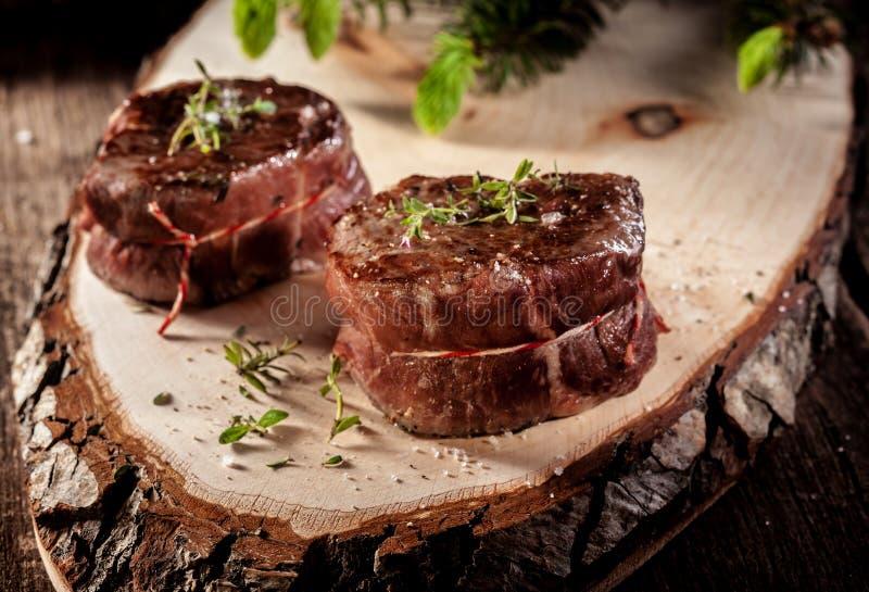 Raccordi della bistecca della carne di cervo serviti sulla plancia di legno rustica immagini stock