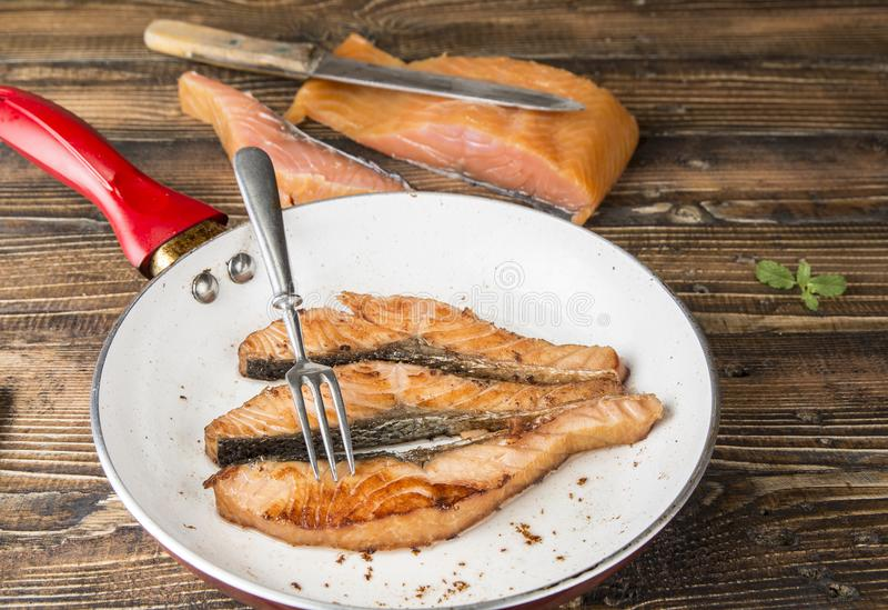 Raccordi di color salmone fritti sulla pentola sul legno immagine stock libera da diritti