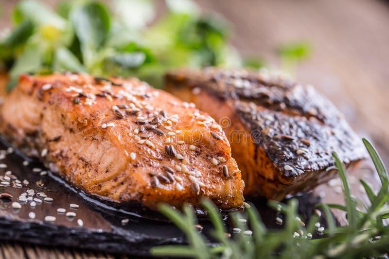 Raccordi di color salmone grezzi Salmone arrostito, decorationon dell'erba dei semi di sesamo sulla pentola d'annata o bordo nero fotografia stock