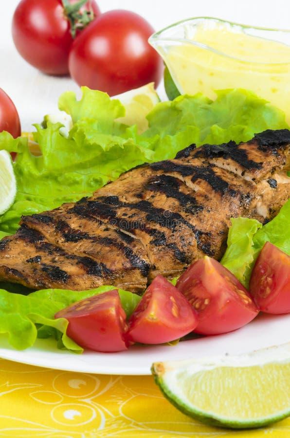 Raccordo arrostito del pollo con le verdure e la calce al piatto bianco immagini stock