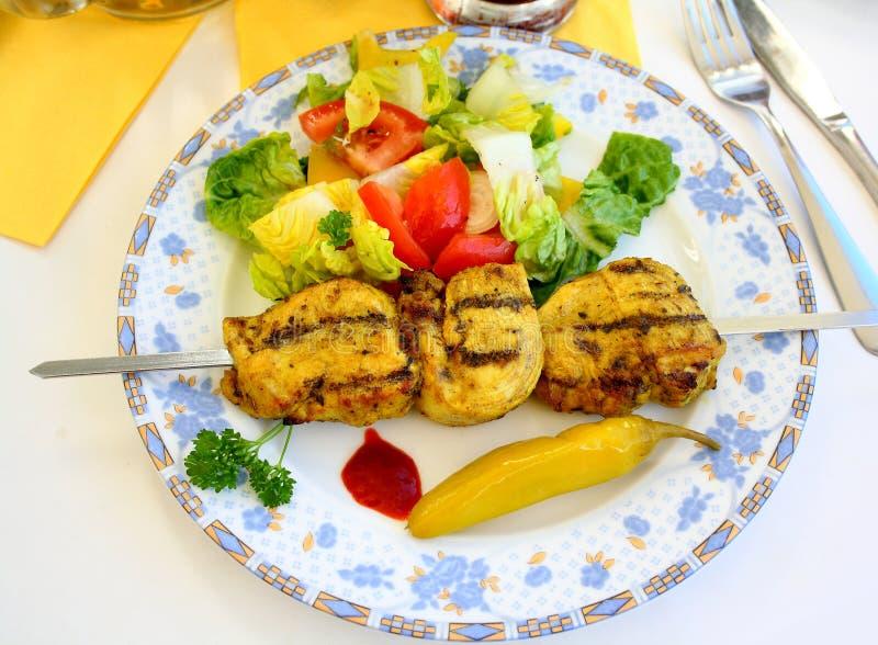 Raccordo arrostito del pollo sullo spiedo del metallo con insalata fotografia stock libera da diritti