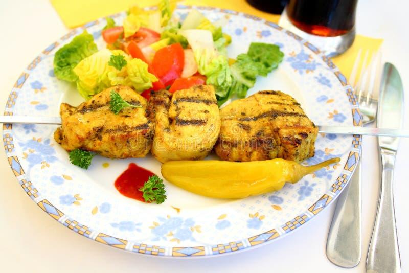 Raccordo arrostito del pollo sullo spiedo del metallo con insalata, fuoco molle fotografia stock libera da diritti