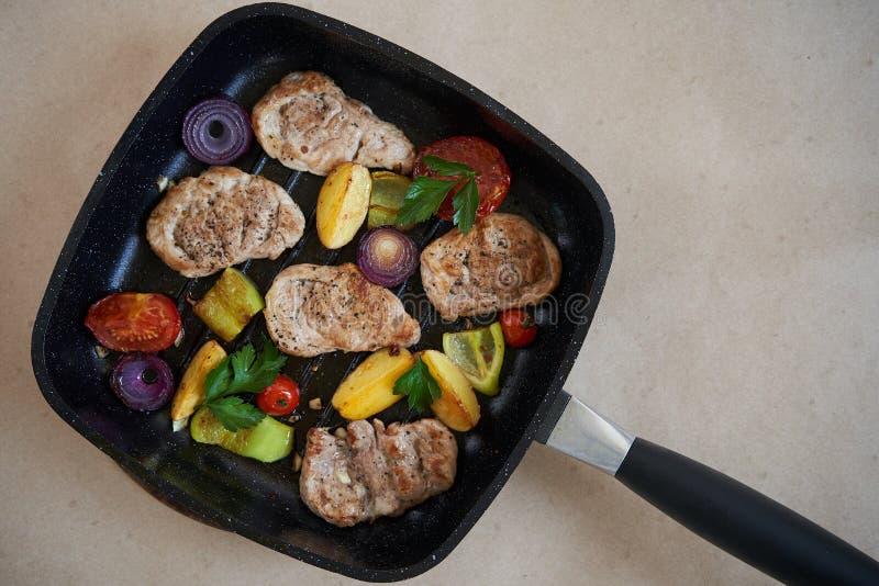 Raccordo arrostito delle bistecche della carne di maiale in padella sopra fondo bianco, vista superiore fotografie stock