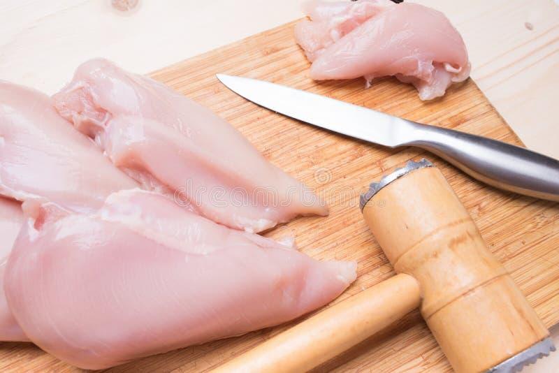 Raccordo, coltello e martello freschi del pollo per battere carne su un fondo di legno immagini stock libere da diritti