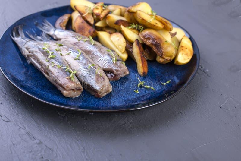 Raccordo dell'aringa su un piatto e al forno nelle patate del forno Alimento tradizionale delizioso dell'Olanda Squisitezza oland fotografia stock