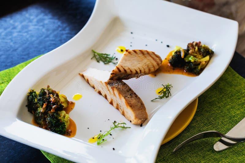 Raccordo della Turchia con i broccoli e la salsa piccante in un piatto bianco immagine stock libera da diritti