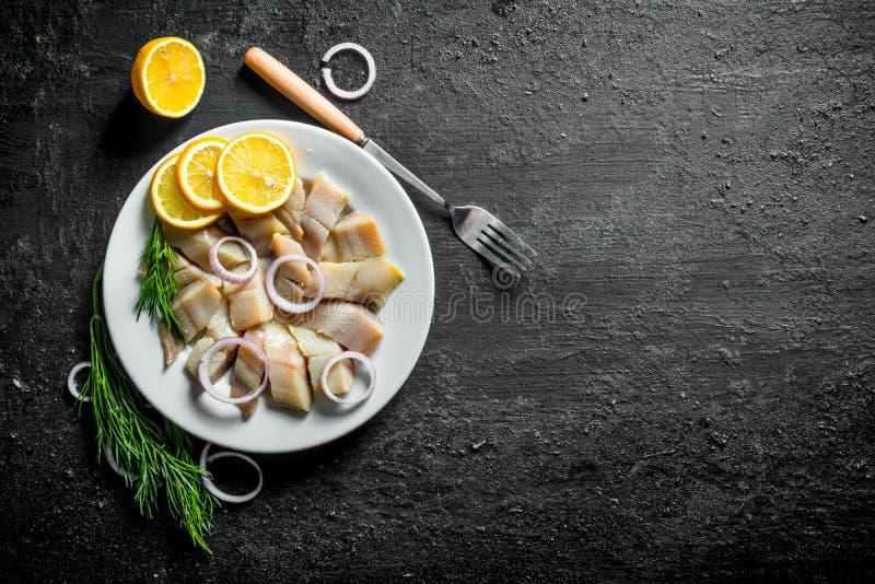 Raccordo di aringa salato con gli anelli di cipolla fotografie stock libere da diritti