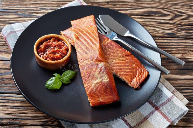 Raccordo di color salmone al forno su una banda nera con la salsa di pomodori seccata al sole su una vecchia tavola di legno fotografia stock