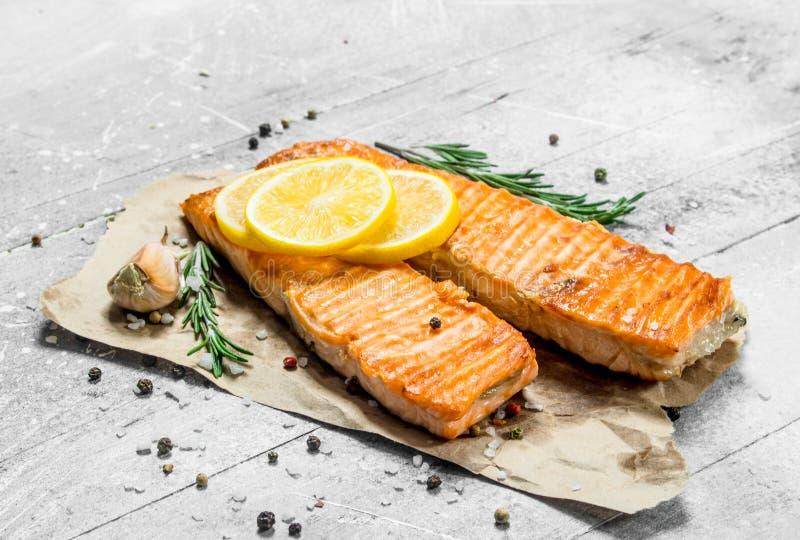 Raccordo di color salmone arrostito con le fette di limone fresco fotografie stock