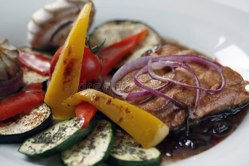 Raccordo di color salmone arrostito e verdure arrostite su un piatto bianco della porcellana fotografie stock libere da diritti