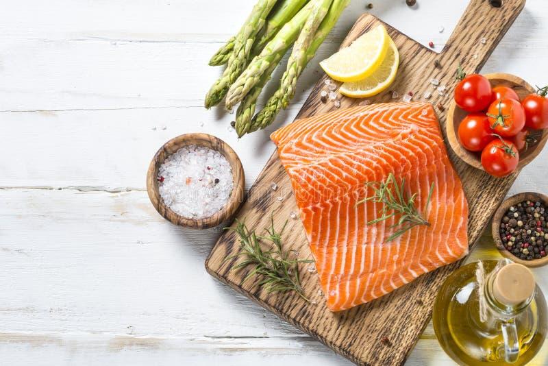 Raccordo di color salmone con gli ingredienti per la cottura - ortaggi freschi a fotografie stock libere da diritti