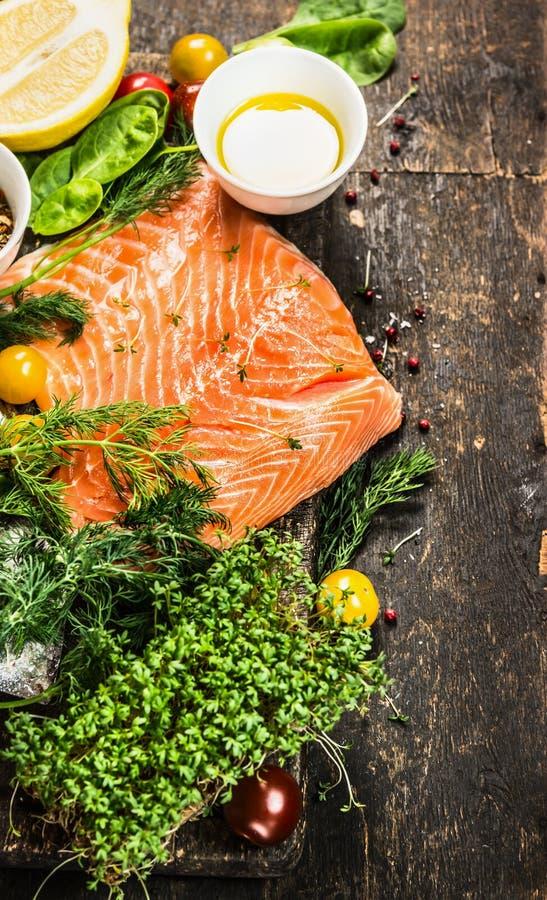 Raccordo di color salmone con petrolio e gli ingredienti freschi per la cottura sul fondo di legno rustico, vista superiore immagine stock