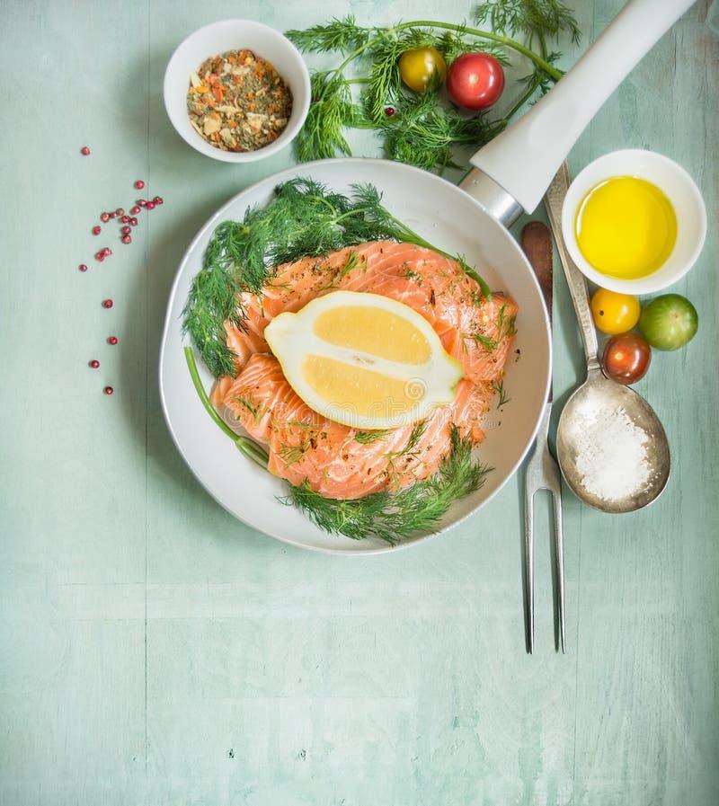 Raccordo di color salmone crudo in padella ed ingredienti freschi per la cottura, vista superiore immagine stock