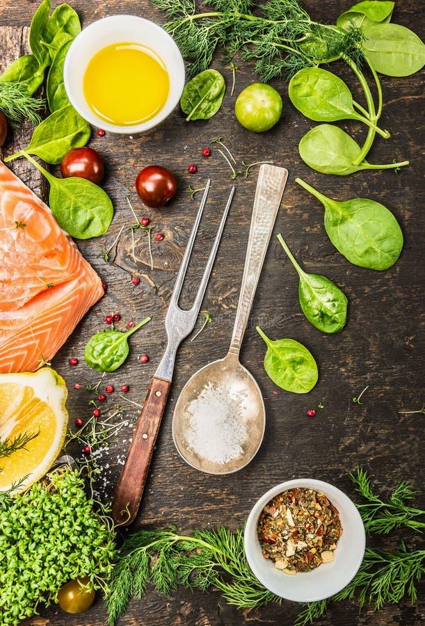 Raccordo di color salmone crudo, preparazione con condimento fresco, petrolio e limone su fondo di legno rustico fotografia stock