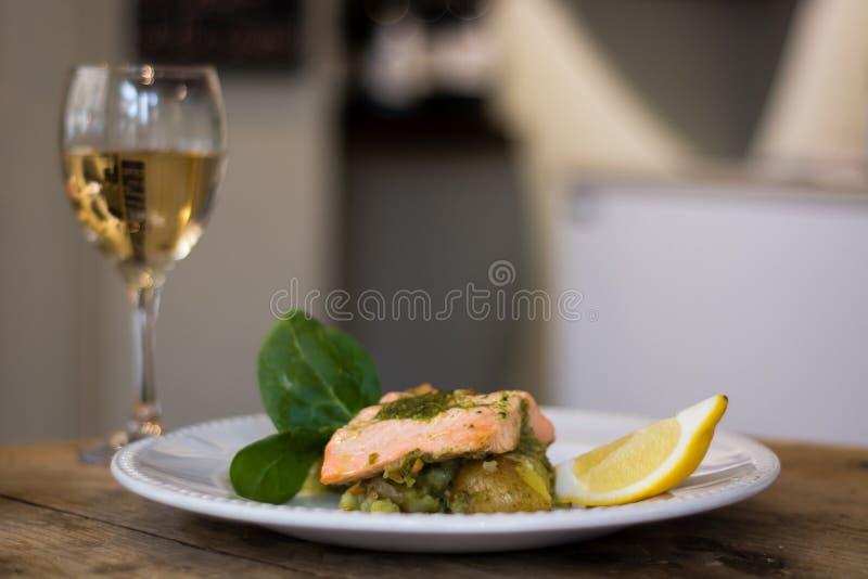 Raccordo di color salmone, pesto e piatto schiacciato della patata con vino immagini stock