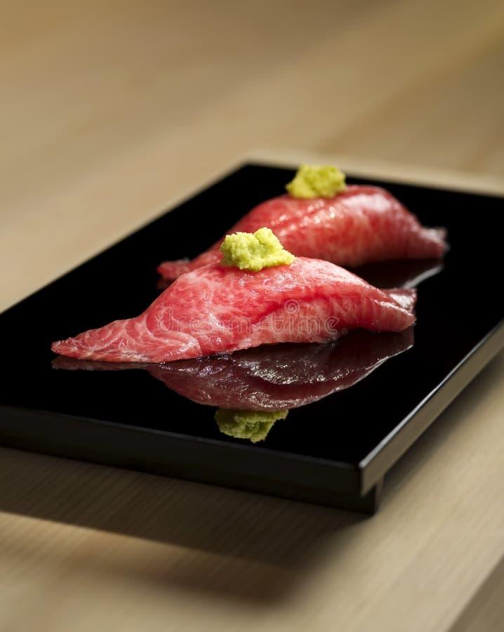 Raccordo grasso di Tuna Sushi con wasabi sul vassoio nero fotografia stock libera da diritti