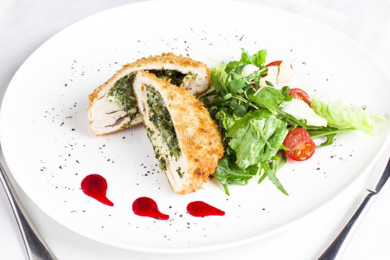 Raccordo impanato del pollo farcito con spinaci con la verdura fresca immagine stock