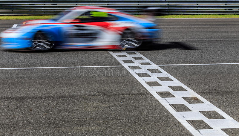 Race car racing on speed track. With motion blur crossing finish line royalty free stock photos