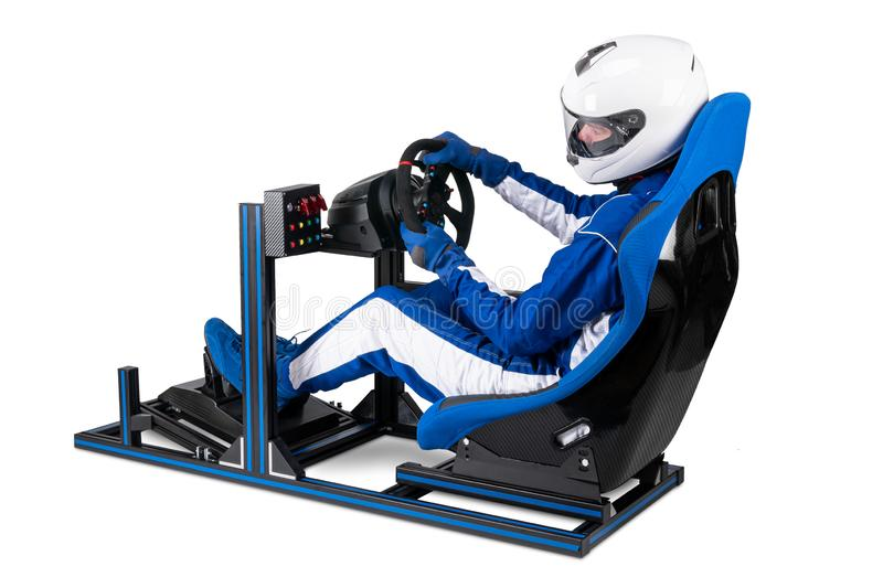 Race driver in blue overall with helmet taining on simracing aluminum simulator rig for video game racing. Motorsport car bucket. Seat steering wheel pedals royalty free stock photography