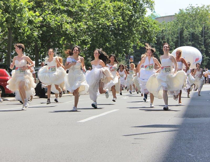Race i bröllopsklänningarna royaltyfria foton
