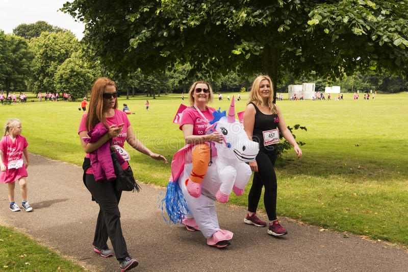 Race for Life sponsored fun run. Liverpool, UK - June 26, 2016: Race for Life sponsored fun run for British charity Cancer Research UK. The race is on, Groups stock image