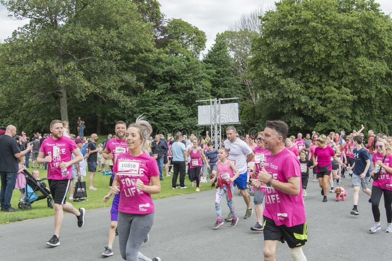 Race for Life sponsored fun run. Liverpool, UK - June 8, 2019: Race for Life sponsored fun run for British charity Cancer Research UK. The race is on, Groups and royalty free stock photo