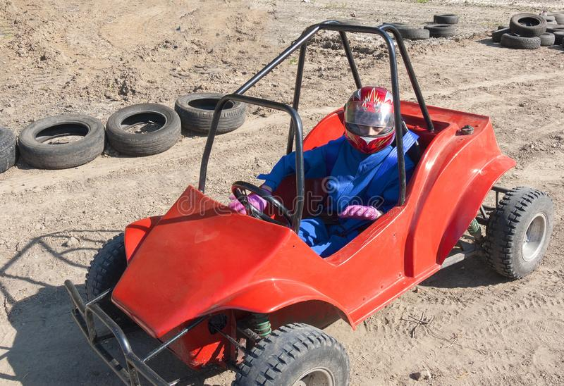 Race of a teenager on a children`s buggy along the sand track stock image