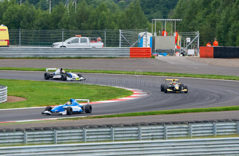 Racecars on the Moscow Raceway circuit. FEDYUKOVO, RUSSIA - JULY 15: Racecars pass the turn on the Moscow Raceway circuit during WSR Formula Renault 2.0 race on royalty free stock photography