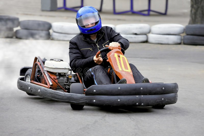 Racer. Man drives his kart on twist with high speed stock image