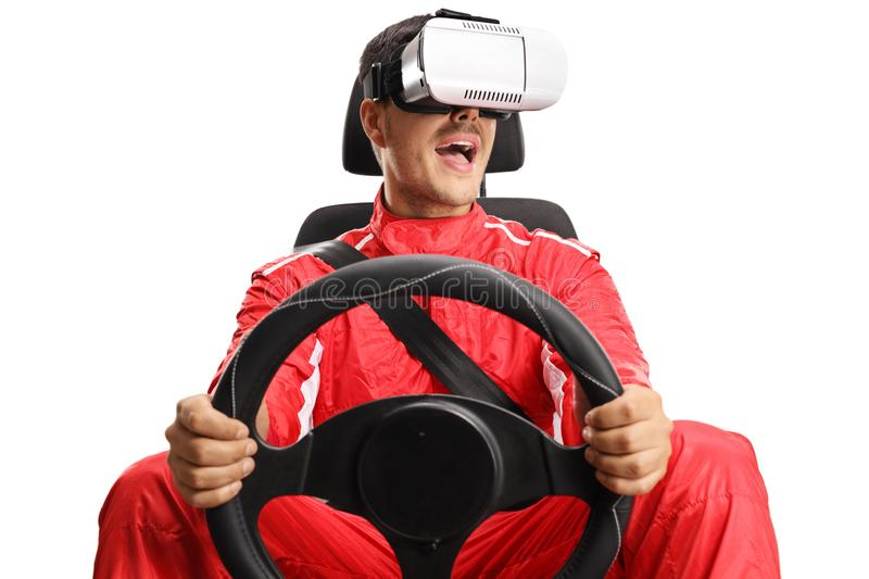 Racer in a car seat holding a steering wheel and wearing VR headset royalty free stock image