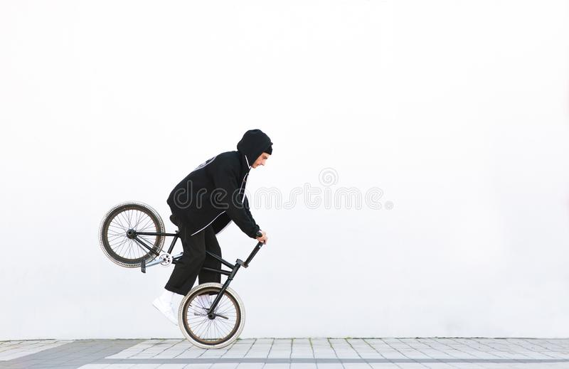 Racer makes a trick in against the background of a white wall. Bmx rider with a bicycle in flight on a white background royalty free stock photos